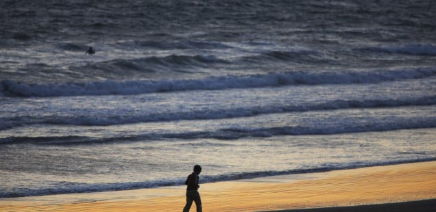 A lone person jogging on the beach at sunset